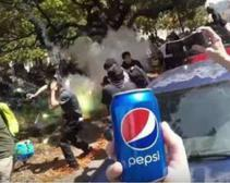 A man attempts to hand police a Pepsi at a similar protest in Berkeley.
