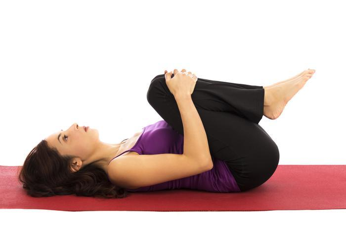 Knee-to-chest exercise from physiotherapist advice for managing pain at home-Active Times